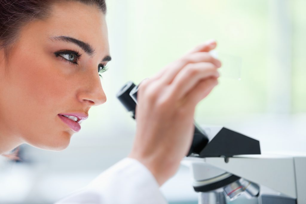 Young woman looking at a microscope slide